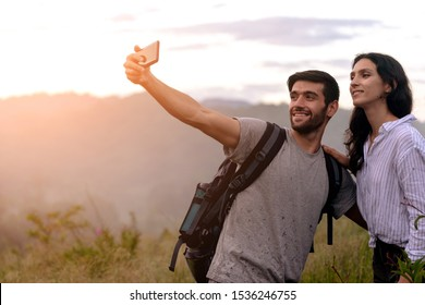 Couple taking Selfie Photo with Smart Phone Hiking on Mountain. Caucasian Woman and Man Hikers Smiling Happy taking a selfie in the Nature. Hiking Couple Concept.