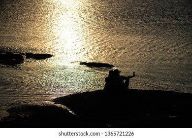 A couple taking a selfie at sunset by the shore
