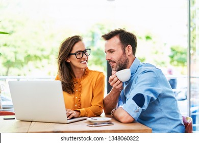 Couple talking at cafe using laptop and drinking cofee