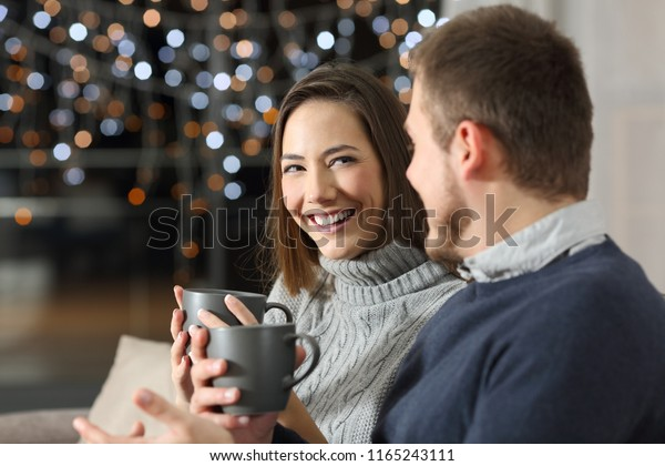 Couple talking in the night in winter sitting on a couch in the living room at home