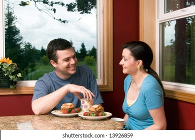 A couple talking over breakfast by a large window, with picturesque background, at home.  Horizontally framed shot.