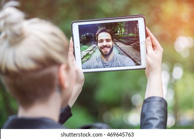 a couple talking over a video call, by using a tablet.