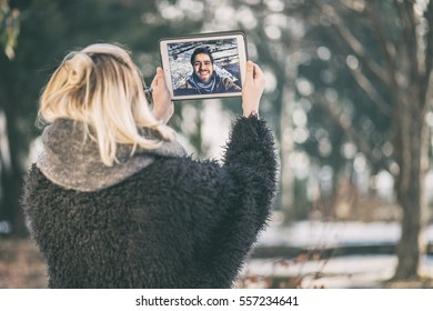 a couple talking over a video call, by using a tablet. young woman chatting to her long distance boyfriend using a tablet outdoors on a sunny winter day.