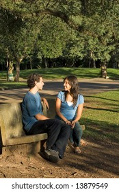 Couple talking and smiling as they sit together on a park bench. Vertically framed photograph.