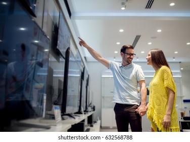 Couple at tech store shopping new tv. Looking for a new big screen for home.