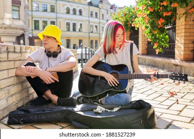 Couple of teenage hipsters street musicians making money by music, girl with colored hair singing and playing acoustic guitar. Teenagers sitting on sidewalk on city street