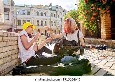Couple of teenage hipsters street musicians making money by music, girl with colored hair singing playing acoustic guitar, guy records video on smartphone. Teenagers sitting on sidewalk on city street