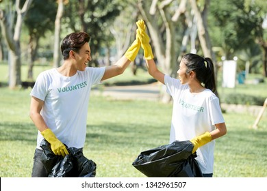 Couple of teenage volunteers standing with garbage bags and giving high-five to each other after cleaning the forest