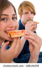couple of teenagers eating pizza