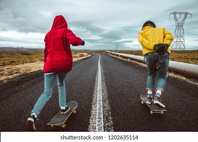 Couple of teenagers having fun skating and making downhill in Iceland