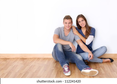 Couple of teenagers sitting against white wall