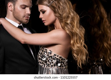 Couple in the tender passion. Black background. Mirror.