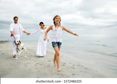 A couple and their daughter walking the dog on the beach