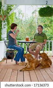 A couple with their dogs enjoying a glass of ice tea on their porch
