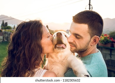 Couple with their puppy dog at sunset. Concept of love between dogs and people