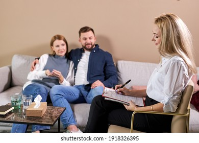 Couple therapy. Nice pleasant caucasian couple visiting professional psychologist and having psychological session in office, sit having conversation. focus on psychologist