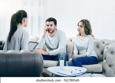 Couple therapy. Nice serious pleasant couple visiting a psychologist and having a psychological session while dealing with problems in relationships
