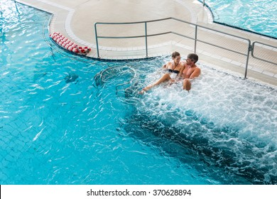 Couple in thermal wellness spa on water massage enjoying the treatment