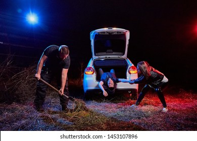 Couple of thugs near car and dead young guy in the trunk at night time and colored red and blue light around. Photoshoot about life of gangsters in Russia