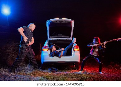 Couple of thugs near car trying to kill young guy in the trunk at night time and colored red and blue light around. Photoshoot about life of gungsters in Russia