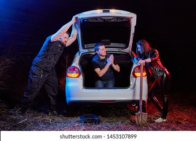 Couple of thugs near car and young guy in the trunk at night time and colored red and blue light around. Photoshoot about life of gangsters in Russia