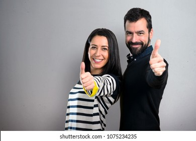 Couple with thumb up on grey background