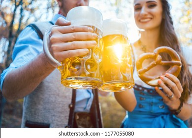 Couple toasting with beer in Bavaria in fall or autumn