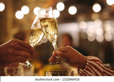 Couple toasting champagne glasses at party. Close up of man and woman hands cheering with wine glasses at a night party.