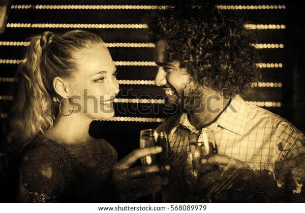 Couple toasting glass of champagne in bar against grey background