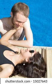 A couple together, near the poolside. The woman is lying down touching the mans face and the man is in the pool staring at her. - vertically framed