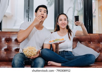 Couple together watching television show movie horor,action,comedy funny reaction sitting relaxation eating popcorn and fruits on sofa couch comfortable in living room at home