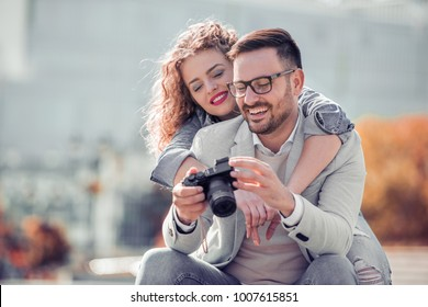 Couple of tourist having fun in the city,taking photo.