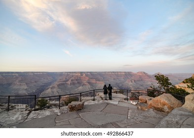 A couple tourist looking at Grand Canyon skyline scenery at Mather Point on the South Rim Trail, Arizona in horizontal view with evening sunlight on rocky cliffs in white cloud and bright blue sky