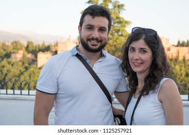 Couple of tourist portrait with La alhambra in the background