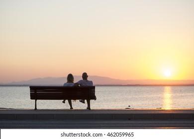 Couple of Tourist Sitting on Bench Watching the Sunset in La Manga, Mar Menor Side, Cabo de Palos, Cartagena and San Javier, Murcia, Spain, Europe