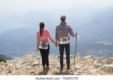 couple of tourists admire the view from the mountain