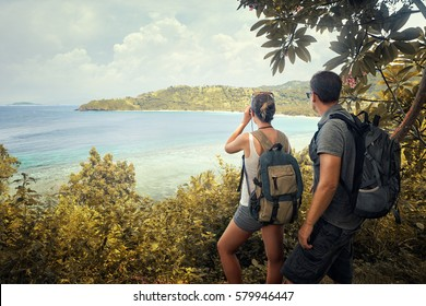 Couple tourists with backpacks enjoying view coast island Lombok on top of a mountain.Traveling along mountains and coast, freedom and active lifestyle concept.