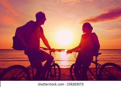 Couple tourists with Bicycles Watching Sunset. Summer Nature Background with Beautiful Sky and Sea. Active Leisure Concept.