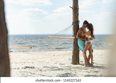 couple of tourists embracing on beach with hammock near the sea