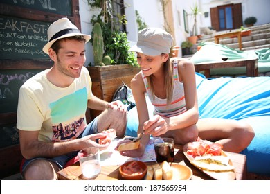 Couple of tourists having finger food in cosy place
