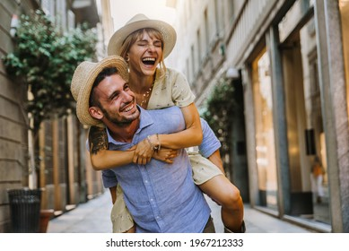 Couple of tourists having fun walking on city street at holiday - Happy friends laughing together on vacation - People and holidays concept