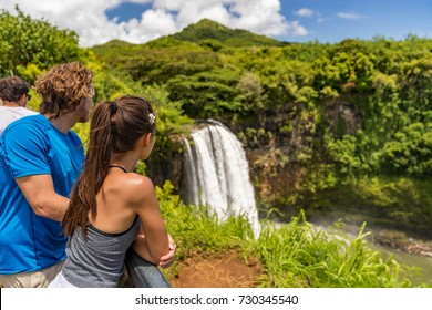 Couple tourists at Hawaii Kauai waterfall. Tourist visiting the Wailua Falls of Kauai Hawaii, hiking nature mountain vacation USA travel.