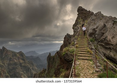 Couple of tourists hiking in the mountains of Madeira from Pico do Areeiro (Arieiro) to Pico Ruivo on a cloudy summer day on October 13, 2015