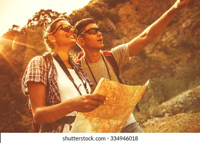 Couple of tourists hiking. Using map to get good direction.