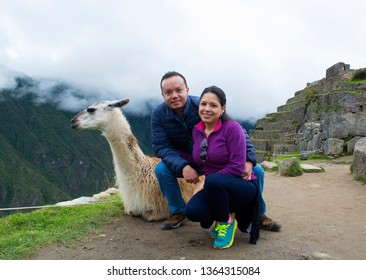 Couple of tourists and llama sitting in front of Machu Picchu, Peru.