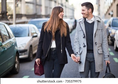 Couple of tourists, a man and a woman, walking down the street in the city of Madrid, Spain