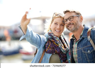 Couple of tourists on vacation taking selfie picture with smartphone