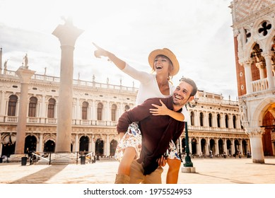 Couple of tourists on vacation in Venice, Italy - Two lovers having fun on city street at sunset - Tourism and love concept - Shutterstock ID 1975524953