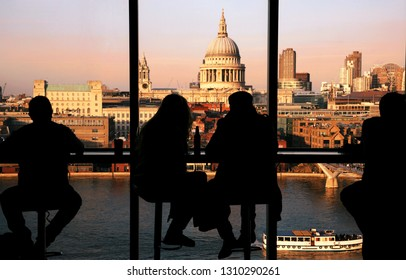 A couple tourists over looking St Paul's Cathedral and Millennium Bridge from Tate Modern at sunset. A tour boat passing through Thames River present.