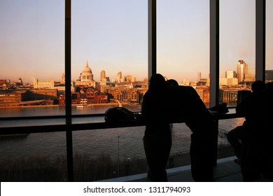 A couple tourists over looking St Paul's Cathedral and Millennium Bridge from Tate Modern at sunset.
